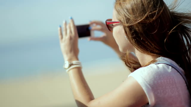 Young beatiful woman travel, sightseeing in tourist bus - happy teenage girl in sunglasses taking picture by smart phone video