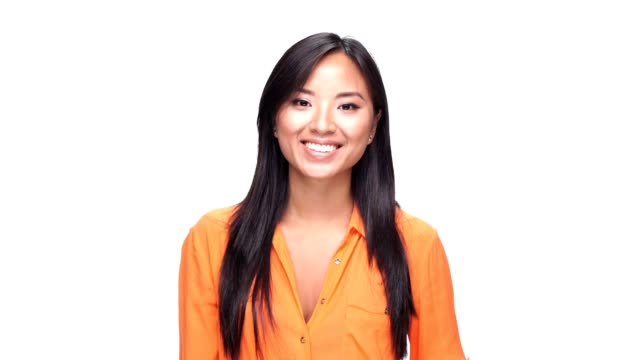 Young beautiful asian woman smiling over white background. video