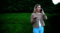 Young beautiful blond female talking on phone angry, indignant video