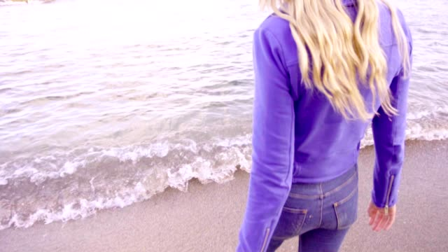 Young beautiful blonde woman goes by the sea shore video