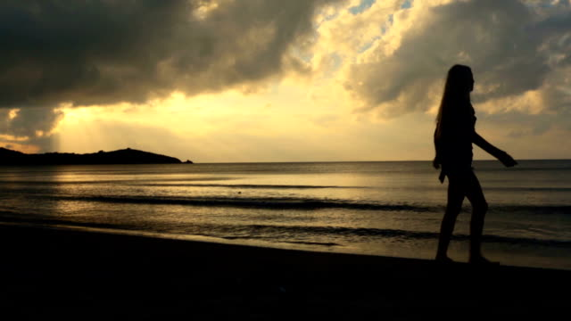 Young beautiful blonde woman silhouette walk on shore at sunset in summer outdoor - gimbal steadicam HD video footage video
