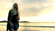 Young beautiful blonde woman walk on shore at sunset in summer outdoor - gimbal steadicam HD video footage video