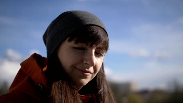Young beautiful brunette with bangs girl with brown eyes in a gray hat and orange jacket stands on a blue sky background with a serious view on the side, smiling and looking straight. Close-up video