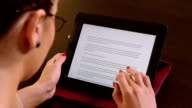 Young beautiful business woman sitting at a table and reading on tablet pc video