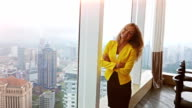 Young beautiful business woman staying by the window at modern building. Female modal looking in the city through window video
