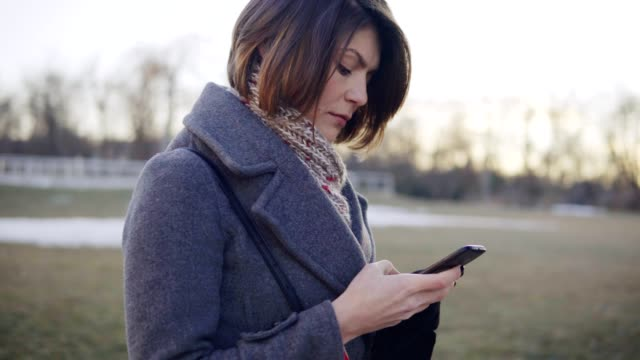 Young beautiful business woman using smartphone, surfing the Internet. video