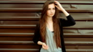 Young beautiful caucasian brown hair woman posing outdoor in the city, looking away pensive leaning back on brown wall. Serious expression, melancholy mood, serene concept video