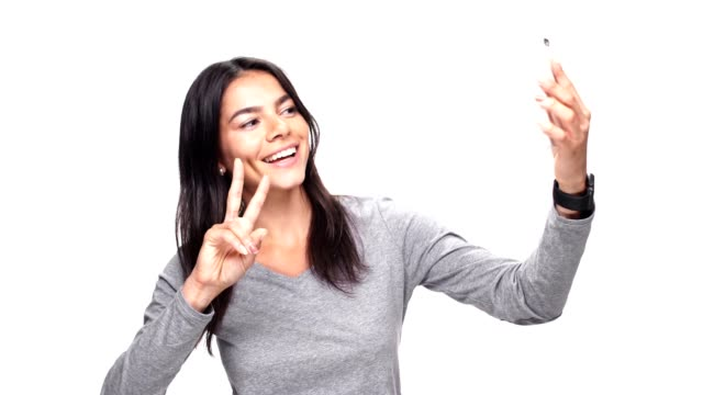 Young beautiful caucasian woman make selfie by phone over white background. video