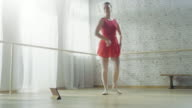 Young Beautiful Contemporary Dancer in Red Tutu Dress Turns on Music on Her Tablet Computer and Starts Dancing Energetically. Shot on a Sunny Day in a Bright Modern Studio. video