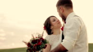 young beautiful couple bride and groom dancing and laughing in the park at sunset on the day of their wedding video