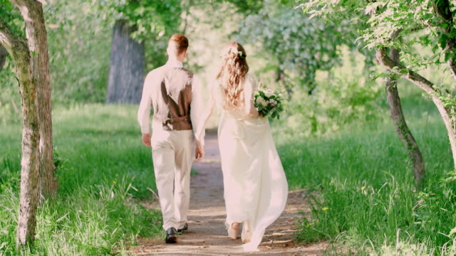 Young beautiful couple walking in the park , holding hands . video