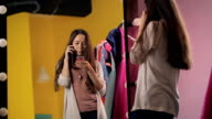 Young beautiful female is talking on cell phone standing in front of mirror video