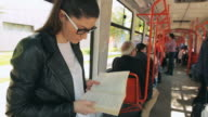Young beautiful female reading a book in train or cable car. video