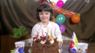 Young beautiful girl blowing candles on a birthday cake video