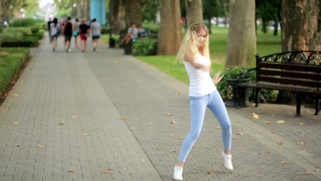 young beautiful girl dancing in a park. woman in jeans dancing in the street video