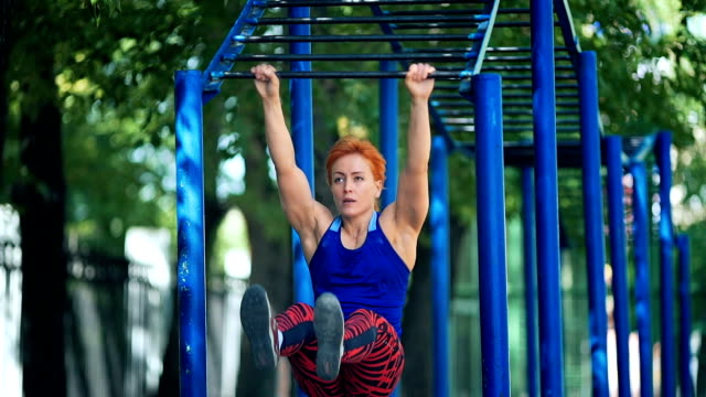 Young beautiful girl doing exercise on a horizontal bar. video