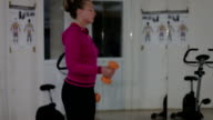 Young beautiful girl goes in for sports use a dumbbell in the gym video