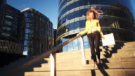 Young beautiful girl in a yellow jacket coming down on stairs. Business woman walking from work in the business center. Bright sunlight in the evening. Cinematic style video video