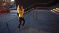 Young beautiful girl in a yellow jacket coming up the stairs. Business woman walking to work in the business center. Bright sunlight in the morning. Cinematic style video video