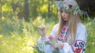 Young beautiful girl in the national ornament embroidered shirt , sitting on the grass near the fire and weaves a wreath for divination video