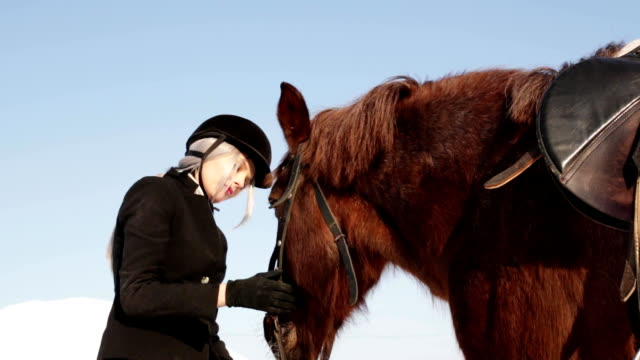 Young beautiful girl jockey caring for a horse in winter video