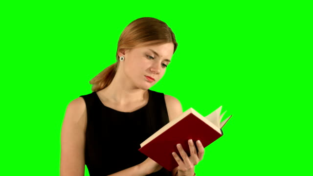 Young beautiful girl reading a book on laptop on a Green Screen, Chroma Key video