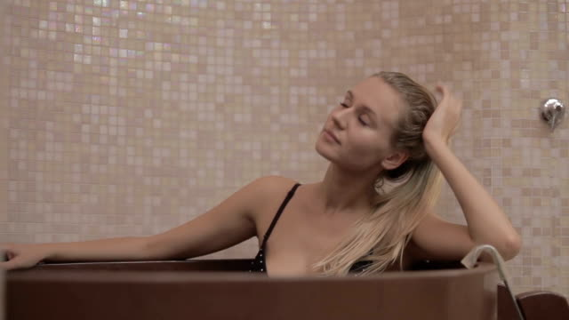 Young beautiful girl relax in the cold water in the wooden bath after hot sauna video
