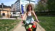 Young beautiful girl riding bike video