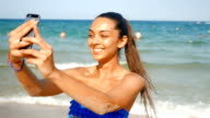 Young beautiful girl taking selfies on the beach video