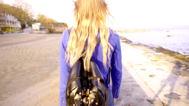 Young beautiful girl walks with her skate board by the sea video