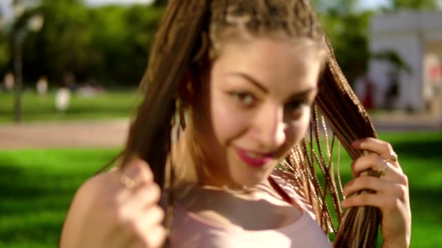 Young beautiful girl with dreads dancing in a park. Beautiful woman listening to music and dancing during a sunny day. Slowmotion shot. video