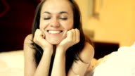 Young beautiful happy woman lying in bed video