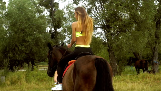 young beautiful lady rides a horse looks back video