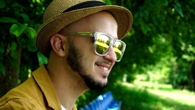 young beautiful man in hat and sunglasses smiling outdoors video