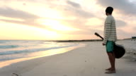 Young beautiful man stands up looking to ocean and sun at beach sea-side at sunrise or sunset in summer - gimbal steadicam HD video footage video