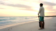Young beautiful man stands up looking to ocean at beach sea-side at sunrise or sunset in summer - gimbal steadicam HD video footage video
