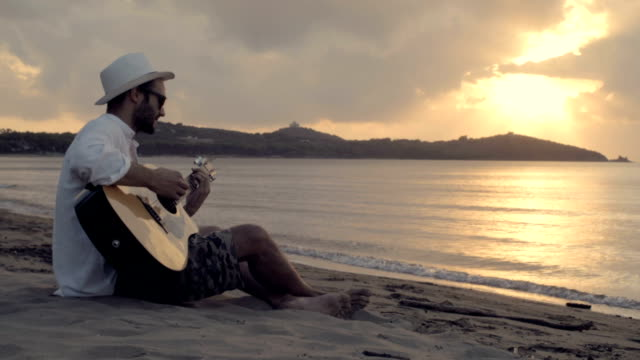 Young beautiful man wearing white panama hat seated outdoor on shore play guitar at sunset in summer - slow-motion HD video footage video