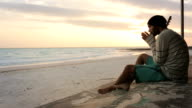 Young beautiful melancholy man on ocean beach sea-side at sunrise or sunset in summer - gimbal steadicam HD video footage video