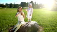 Young beautiful mother and her daughter playing with soap bubbles in the Park. Slow motion. video