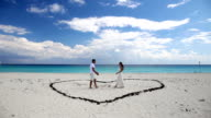 Young beautiful newlyweds meet each other on beach video