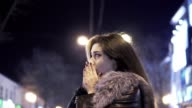 Young beautiful pretty woman heating her hands and waiting for someone at city street in the night against evening lights video