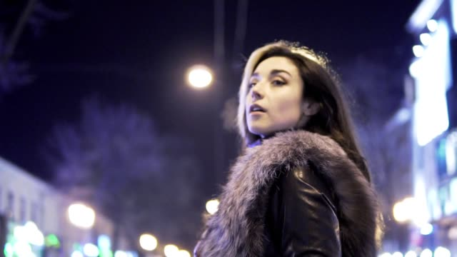 Young beautiful pretty woman posing at city street in the night against evening lights video