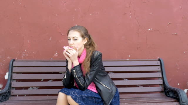 Young beautiful sad girl is sitting on a bench. Sad thoughts, bad news. Yearning and hopelessness. video