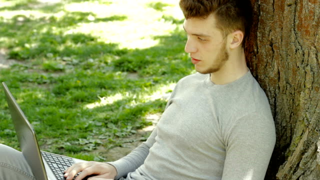 young beautiful student writes on a laptop under a tree in the Park video