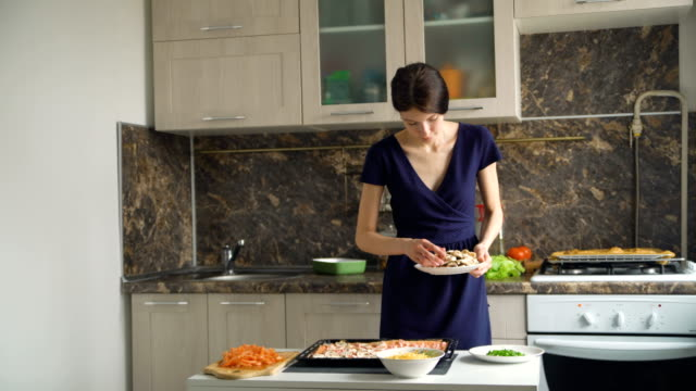 Young beautiful woman cook put mushrooms on pizza dough in the kitchen at home video