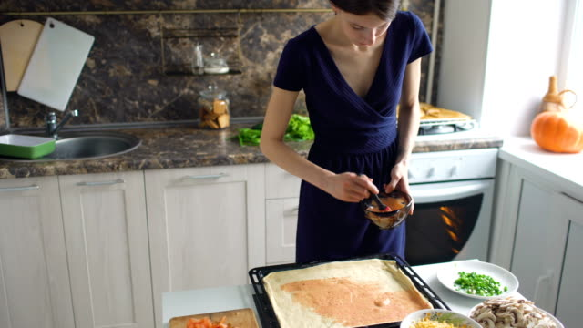 Young beautiful woman cook put sauce on pizza dough in the kitchen at home video