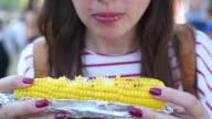young beautiful woman eating corn video