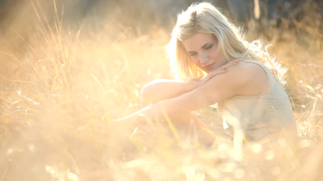 Young beautiful woman in autumn grass video