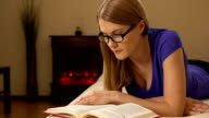 Young beautiful woman in glasses lying on a sofa, reading a book video