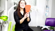 Young beautiful woman in the dental chair. After the procedure she looks in the mirror. The concept of a healthy smile. video